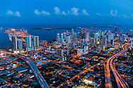 Miami Skyline at twilight with city lights, view looking from west to east with Biscayne Bay and ocean in the background