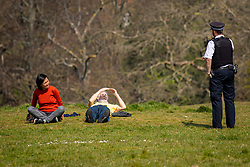 © Licensed to London News Pictures. 09/04/2020. London, UK. A police speaks to two people sat on the grass in Greenwich Park. The government has asked that people continue to remain indoors over the Easter Weekend. Photo credit: Rob Pinney/LNP