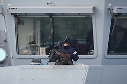 © Licensed to London News Pictures. 20/10/2016. Portsmouth, UK. Crew man a minigun aboard HMS Dragon as she returns to Portsmouth during a time when Royal Navy ships are actively involved with escorting Russian Naval ships from the North Sea through the English Channel as they make their way to the Mediterranean.  Photo credit: Rob Arnold/LNP