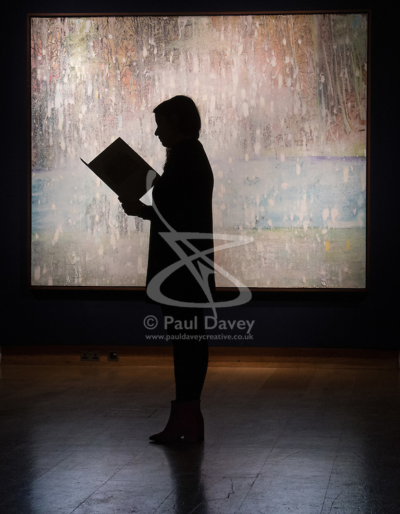 Christie's, London, March 3rd 2017. PICTURED: A woman admires Peter Doig's 'Coburg 3+1 More', painted in 1994 which is estimated to fetch between £8-12 million.  <br /> Fine art auctioneers Christies hold a press preview for their Post-War and Contemporary Art auctions to be held on March 7th and 8th.