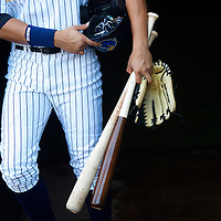A player emerges from the stadium tunnel laden with bats, gloves, and a batting helmet, before a game in which New York Yankees Third Baseman Alex Rodriguez played for the AA Trenton Thunder in Trenton, NJ on August 3, 2013.  Rodriguez is facing a suspension by Major League Baseball for his alleged use of steroids with the Biogenesis clinic in Florida.
