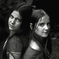 Two young teenage females with long hair standing back to back looking at camera