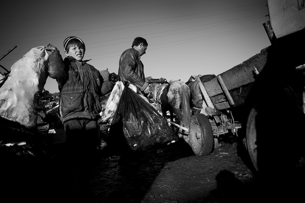 (01/12/2007) A young Albanian boy helps his father and brother unload their cart after having spent a day collecting scrap to sell on to a junkyard, on the main road between Pristina and Mitrovica, Kosovo. The father of the family earnt 11 euros for the days work which had to help support his ten children. (photo: Greg Funnell)