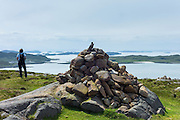 Tourist views The Summer Isles, part of the Inner Hebrides, and the Outer Hebrides from by a cairn at Altandhu, the West Coast of Scotland
