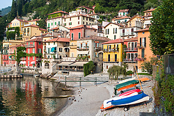 A shoreside view of Varenna, known for its lakeside walk and colorful buildings stretching up the mountain above Lake Como, Italy.