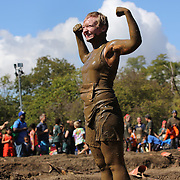 Joyous competitors after tackling the mud pit during the New York Merrell Down and Dirty Obstacle Race presented by Subaru. Over 6000 competitors took part in the event which included mud pits, water crossings, slippery mountain, cargo nets, monster climb and ladder walls. The event was held at Pelham Bay Park The Bronx, New York. 29th September 2013. Photo Tim Clayton