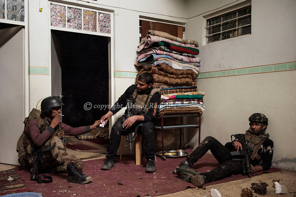 Iraq, Mosul: Golden Division members take a rest during a house by house advance in west Mosul. Alessio Romenzi