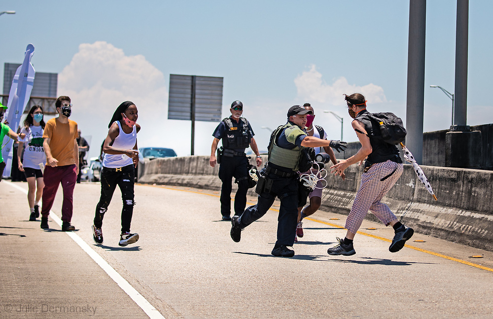 Nathan Durapau runs away from a Jefferson Parish Sherriff Deputy during a protest organized by the families of Modesto Reyes, Keeven Robinson, Darivi Robertson,Chris Joseph, Armond Jairon Brown Eric Harris and Leo Brooks - black men killed by the Jefferson Parish Police since 2018. He was one of 5 people arrested. at the protest where family members are calling for accountability from the Jefferson Parish Sheriff's Office and for the officers to be required to wear body cameras.