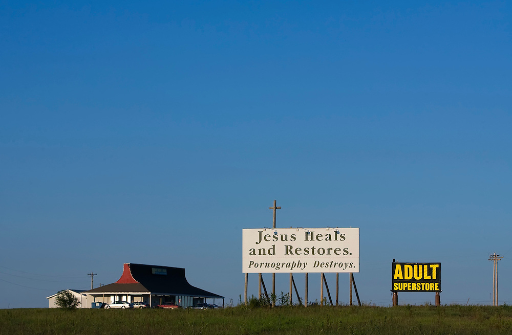 The signage for the Lion's Den Super Store west of Abilene, Kansas on Interstate 70 has been a subject of controversy. Kansas Attorney General Steve Six filed an agreement that says the state won't enforce a state law that limits the size and content of highway signs advertising adult stores. A religious billboard near Lion's Den stands in protest.