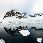 "Some of the rugged mountains rising up along the shore of the Lemaire Channel are reflected on glassy calm waters of the Lemaire Channel on the Antarctic Peninsula's western side. The Lemaire Channel is sometimes referred to as ""Kodak Gap"" in a nod to its famously scenic views."