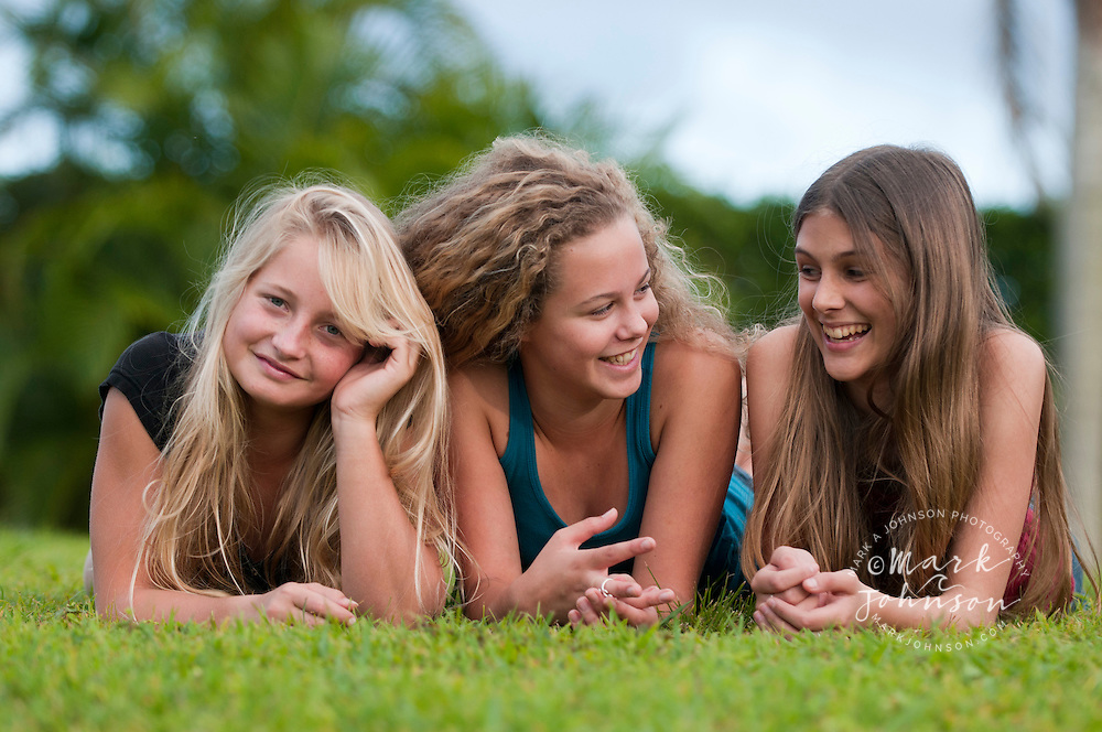 Teenage girls lying in backyard, Kauai, Hawaii