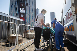 © Licensed to London News Pictures . 21/04/2020. Manchester, UK. One of the first patients to be discharged from the hospital is helped on to an ambulance ahead of being taken home , as an advert telling people to STAY HOME is displayed on the face of the Axis Tower building . The National Health Service has built a 648 bed field hospital for the treatment of Covid-19 patients , at the historical railway station terminus which now forms the main hall of the Manchester Central Convention Centre . The facility is treating patients from across the North West of England , providing them with general medical care and oxygen therapy after discharge from Intensive Care Units . Photo credit : Joel Goodman/LNP