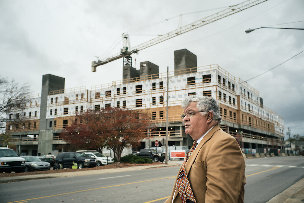 AUBURN, AL – NOVEMBER 20, 2016: Philip Dunlap describes ongoing developments in front of a new student high-rise being built in downtown Auburn. Two similar student housing buildings were recently completed, and an additional two are slated to break ground in the coming months. Dunlap, the city of Auburn's Economic Development Director, worked for the city of Birmingham for nearly a decade until he was recruited by the city of Auburn in 1984 to start the city's Economic Development Program. Since that time, the city has witnessed significant growth and development.<br /> <br /> In much of the United States, global trade and technological innovation has failed to produce the prosperity hoped for by political and business leaders. Yet despite formidable economic challenges, some localities are flourishing. In Lee County, Ala., unemployment is below the national average despite the loss of thousands of manufacturing jobs, and the key to the county's resilience may be Auburn University, which provided a steady source of employment during recessions and helped draw new businesses to replace those that fled. CREDIT: Bob Miller for The Wall Street Journal<br /> [RESILIENT]