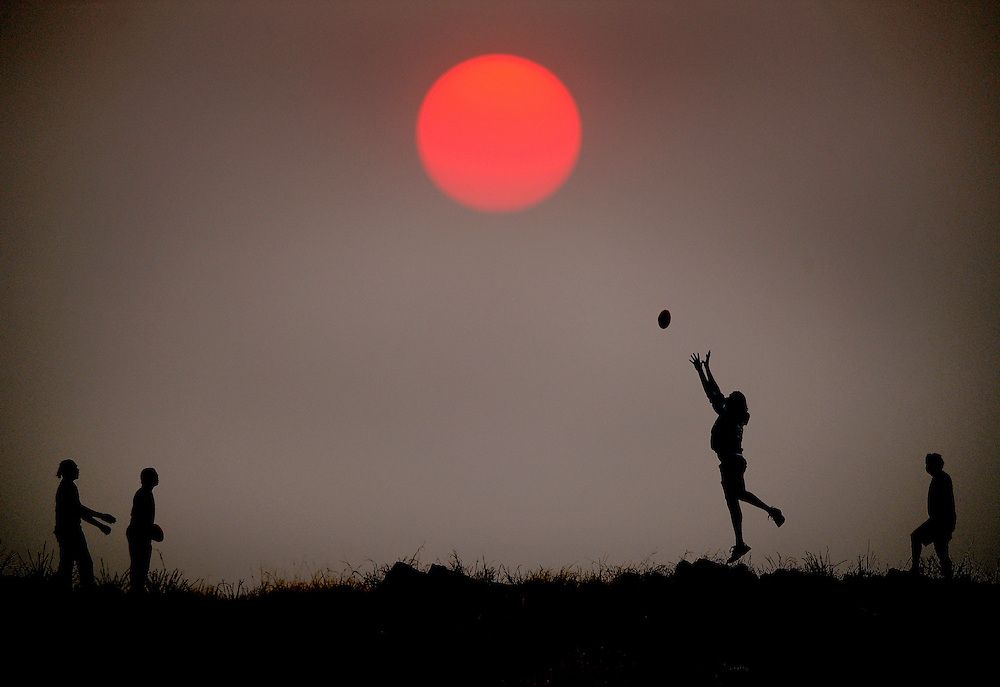 It was heading into the 2011 cricket season but locals up in Alice Springs still preferred some kick to kick with the football at the local rubbish tip during sunset. The crimson sun was thanks to a bush fire way out of town. (Copyright Michael Dodge/Herald Sun)