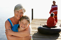 Senior woman hugging grandson (5-6) on dock with two children (7-9) in background.