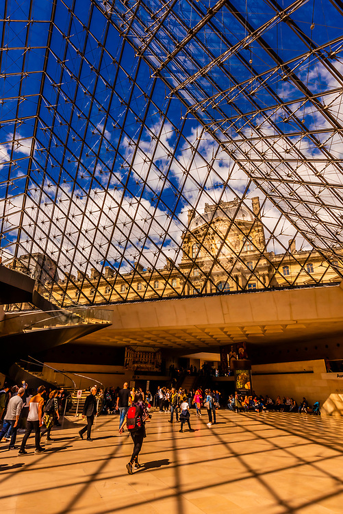 Inside the Louvre Pyramid (Pyramide du Louvre.) It is the main entrance to the Louvre Museum and is a large glass and metal pyramid designed by Chinese-American architect I. M. Pei, surrounded by three smaller pyramids, in the main courtyard (Cour Napoléon) of the Louvre Palace (Palais du Louvre) in Paris. Paris, France.