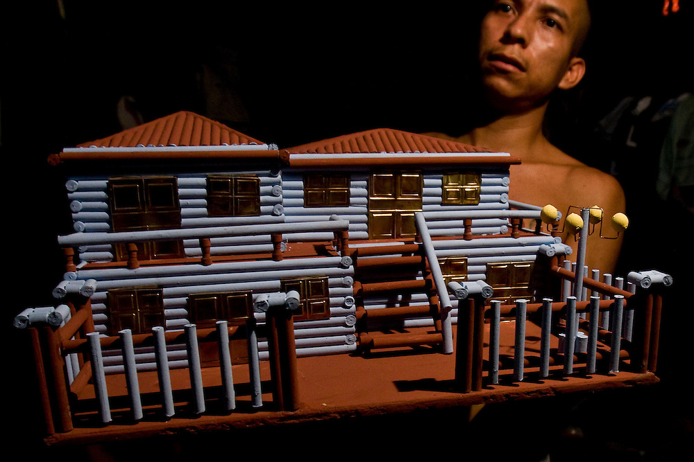 An 18th street gangmember holds up a house he has constructed from rolled up newspaper in a jail in Ciuadad Arce. There are no programs or activities for jailed gangmembers in the countries overcrowded prisions.