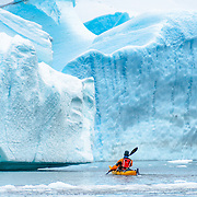 A solo kayaker navigates through an opening between large blue icebergs in an iceberg cemetery in a bay at Melchior Island on the Antarctic Peninsula.