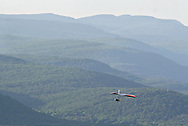 Ellenville, NY - A man flying a hang glider soars above a forest with the Catskill Mountains in the background on May 30, 2009.