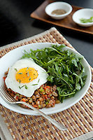 A bowl of lentil salad  with a fried egg and green salad sits on a brown placemat on a dark table