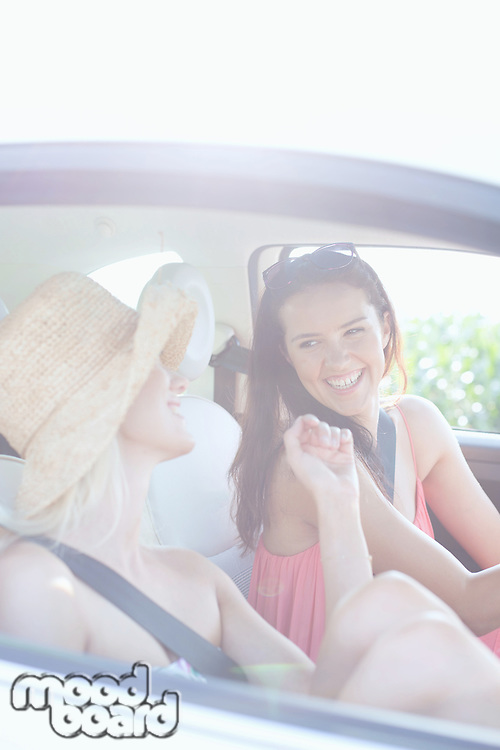 Cheerful female friends enjoying road trip in car
