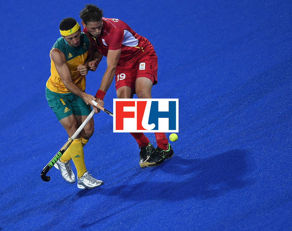 Australia's Jamie Dwyer (L) vies for the ball with Belgium's Felix Denayer during the men's field hockey Belgium vs Australia match of the Rio 2016 Olympics Games at the Olympic Hockey Centre in Rio de Janeiro on August, 9 2016. / AFP / MANAN VATSYAYANA        (Photo credit should read MANAN VATSYAYANA/AFP/Getty Images)