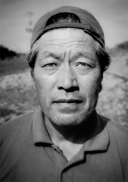 Masami Yoshizawa, a dairy farmer whose farm still sits in the nuclear no-entry zone but, because the entrance to the farm is on the new nuclear no-entry zone line, he has been allowed to live here.  Namie-machi, Fukushima Prefecture, Japan.  The ground is highly radioactive.  Yoshizawa has saved his herd of cows and taken in addition cattle that were running wild inside the zone.  The dairy products and meat is too contaminated with radiation be sold for human consumption.