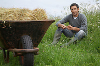 Man sitting beside wheelbarrow with hay in field portrait