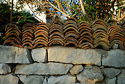 Old, traditional roof tiles on stone wall. Orebic, Croatia.