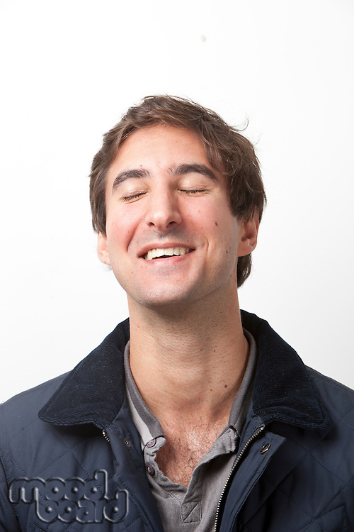 Close-up of young man with eyes closed smiling against white background