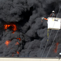 A Pontotoc Electric Company worker watches the blaze from his bucket truck as he disconnets the power lines from the facility in Ecru Friday morning.