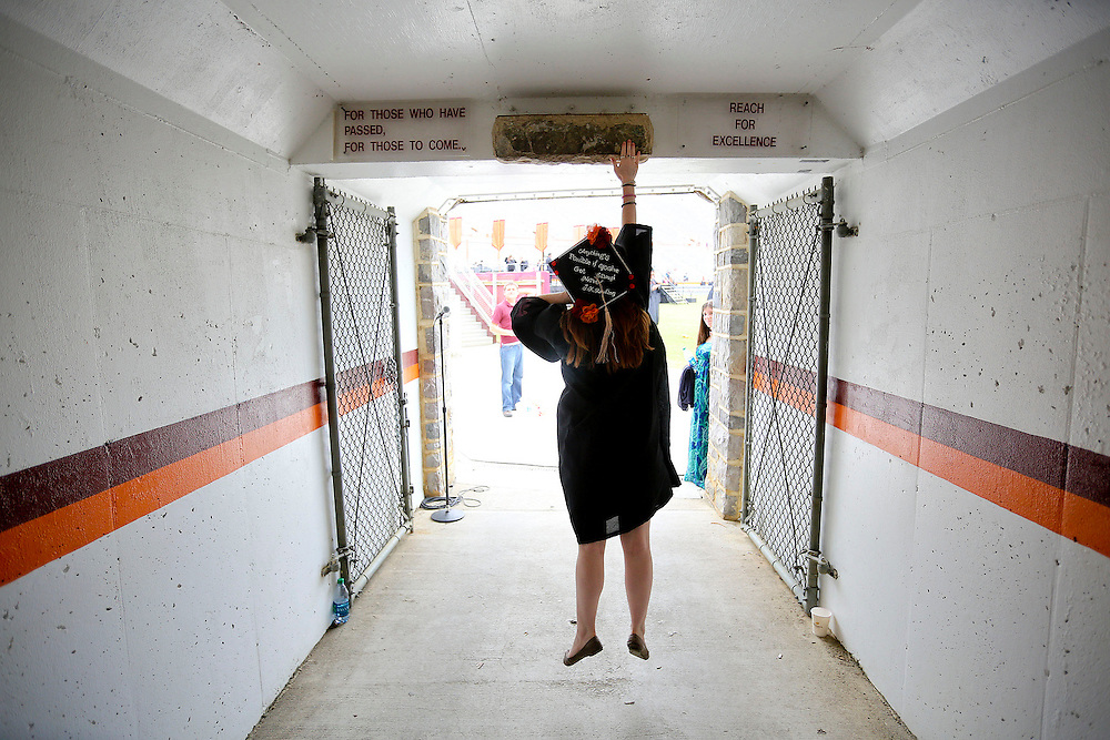KYLE GREEN | The Roanoke Times;<br /> [5/17/2013 Virginia Tech graduating student Emily Moonan turns and jumps to touch the Hokie Stone as she leaves Lane Stadium after the 2013 spring graduation ceremony held on Friday in Blacksburg, Virginia. ]