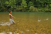 A nine-year-old boy skips a rock on the James River, Missouri.