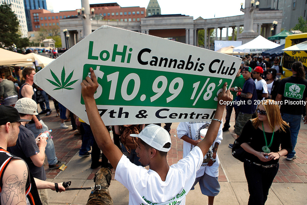 DENVER, CO - APRIL 20: Javier Martinez of Denver, Co. uses a sign to advertise for LoHi Cannabis Club dispensary  as an estimated 10,000 people are expected to gather in Civic Center Park in Denver, Colorado on April 20, 2012 to celebrate the state's medicinal marijuana laws and collectively light up at 4:20pm. On Nov. 6, Colorado may become the first state to legalize marijuana with the passing of Amendment 64, a controversial ballot initiative that would permit up to 1 ounce of possession for those 21 and older. (Photo by Marc Piscotty/ © 2012)