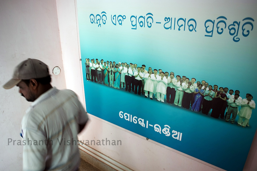 An employee walks past a promotional poster displayed inside the POSCO Kujanga office in Orissa, India, on Thursday July 1, 2010. Photographer: Prashanth Vishwanathan/Bloomberg News