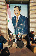 Iraqis sell household items on a Baghdad street in front of one of the ubiquitous portraits of Saddam Hussein.<br />