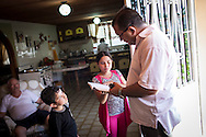 Miguel Angel Viloria (d) revisa la tarea de su hija Yuliana (c), mientras Miguel Alejandro (i) observa. Gracias a FundaHigado, Yuliana recibió un trasplante de higado que le permite disfrutar de la vida. Punto Fijo, Venezuela 26 y 27 Oct. 2012. (Foto/ivan gonzalez)