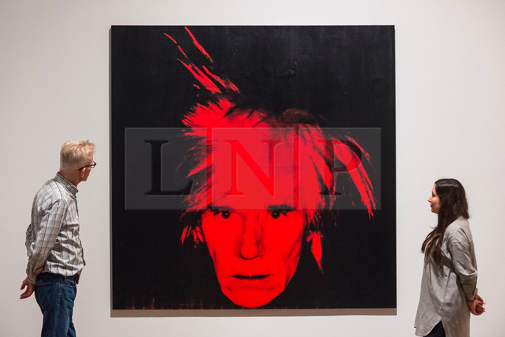 """© Licensed to London News Pictures. 10/03/2020. LONDON, UK. Staff members pose next to """"Self-Portrait"""", 1986, by Andy Warhol. Preview of """"Andy Warhol"""", a retrospective of over 100 works by one of the most recognisable artists of the late 20th century.  The exhibition runs 12 March to 6 September 2020 at Tate Modern.  Photo credit: Stephen Chung/LNP"""