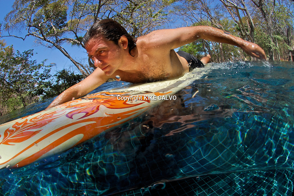 MIguel, employee of the Discovery Program at Peninsula's Papagayo Beach Club teaches visitors he basics of surfing in the development's beach front pool.