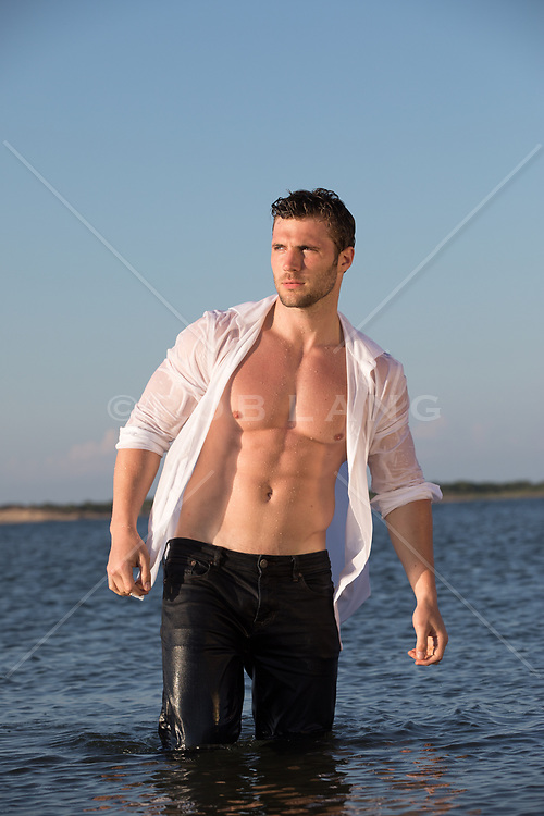hot shirtless man in wet clothes standing in the bay in East Hampton, NY
