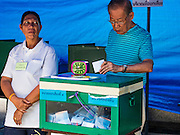 07 AUGUST 2016 - BANGKOK, THAILAND: A man drops his ballot into the ballot box at a polling place in a park in Bangkok. Thais voted Sunday in the referendum to approve a new charter (constitution) for Thailand. The new charter was written by a government appointed panel after the military coup that deposed the elected civilian government in May, 2014. The charter referendum is the first country wide election since the coup.      PHOTO BY JACK KURTZ