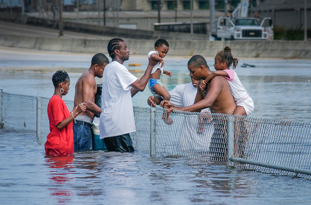 A family passes a toddler over a fence  in New Orleans. The city is under water as a result of Hurricane Katrina and the failed levee system.<br /> August 30, 2005