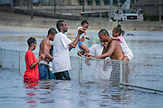 A family passes a toddler over a fence  in New Orleans. The city is under water as a result of Hurricane Katrina and the failed levee system.<br />