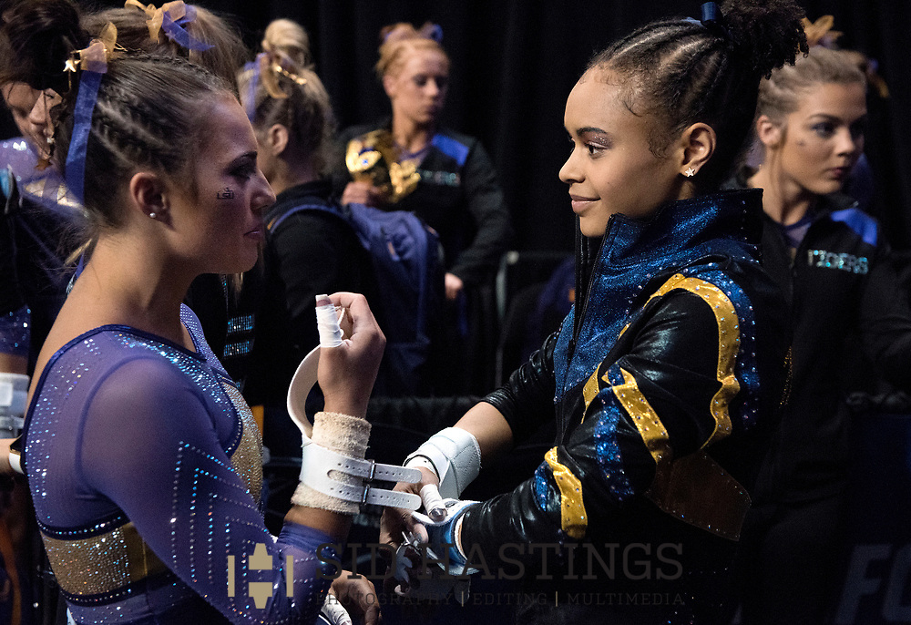 20 APRIL 2018 -- ST. LOUIS -- LSU gymnast Lexie Priessman (left) visits with Michigan gymnast Brianna Brown during the bye preceding the Uneven Parallel Bars during the 2018 NCAA Women's Gymnastics Championship Semifinals in St. Louis Friday, April 20, 2018. LSU finished second in the semifinal, joining UCLA and Nebraska in advancing from the first semifinal into the Super Six championship round on Saturday.<br /> <br /> Photo &copy; copyright 2018 Sid Hastings.