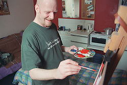 Male resident painting on easel in bedroom of homeless hostel for people with learning difficulties,