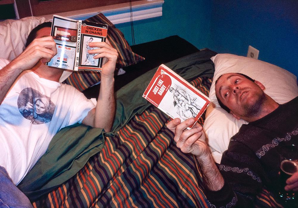 Danny Burke and John Macken reading gay porn in bed