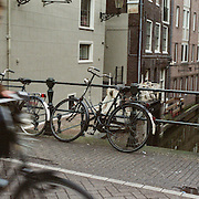 A panoramic view of a cyclist navigating the narrow streets of Amsterdam, Holland. 23rd July 2011. Photo Tim Clayton