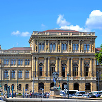 Hungarian Academy of Sciences in Budapest, Hungary<br /> An architectural cornerstone of Széchenyi Square is the Hungarian Academy of Sciences. The Renaissance Revival design by Fredrich Stüler was built in 1865. The mission of this national academy is to monitor, promote and cultivate eleven scientific disciplines. These include linguistics, history, medicine, engineering and biology. The prestigious learned society was founded in 1825 by István Széchenyi. The count was the same influential politician who spearheaded construction of the Chain Bridge where the couple is sitting.