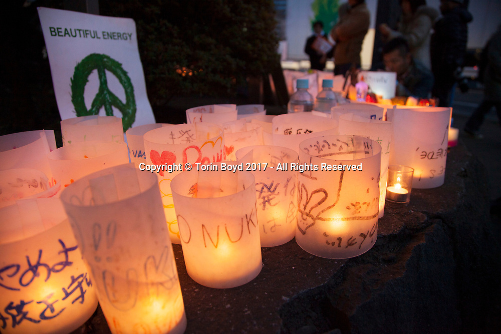 "March 11, 2017, Tokyo, Japan: On the sixth anniversary of the Fukushima Daiichi Nuclear Power Plant disaster caused by a massive tsunami, activists from the group ""Global Candle Chain - 3/11 Sixth Anniversary Remembrance by Beautiful Energy"" lit candles in front of Japan's National Diet Building (parliament). This was for a call to replace nuclear power with safer reusable energy and remember those lost in the quake and tsunami. They also urged followers on Facebook to light a candle today and post a photo of it to their page. This was part of an anti-nuke rally attended by thousands of grass roots activists. The magnitude 9.0 earthquake and tsunami which occurred on 3/11/11 killed more than 22,000 people. (Photo by Torin Boyd)."