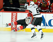 The Kings' Jake Muzzin lays a hard hit on the Blackhawks' Marcus Kruger during the third period of Game 5 of the Western Conference Final of the 2014 NHL Stanley Cup Playoffs at United Center in Chicago Wednesday.